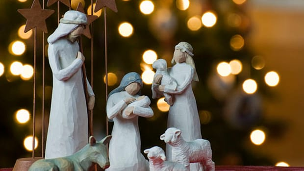 A depiction of the Nativity with a Christmas tree backdrop.
