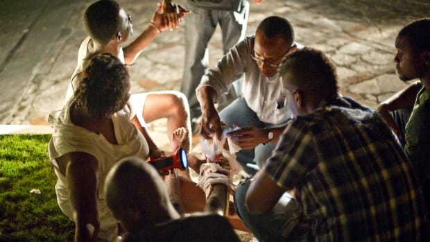 A wounded child gets relief from fellow Haitians on January 12, 2010 in Port-au-Prince, Haiti.
