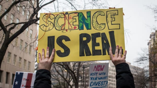 "Photo showing hands holding up a sign that reads, ""SCIENCE IS REAL"""