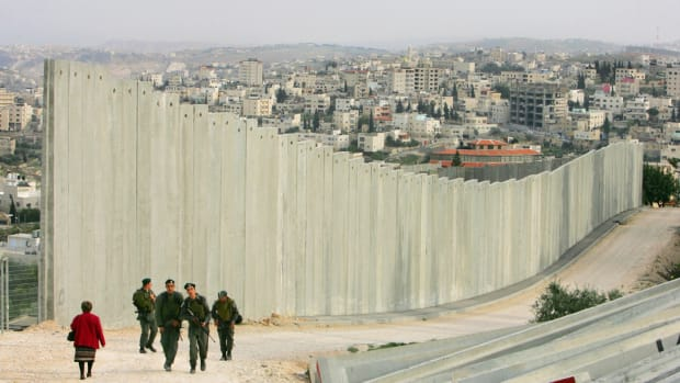 Israeli soldiers patrol in East Jerusalem along the concrete separation barrier bordering Abu Dis, West Bank, in 2006.