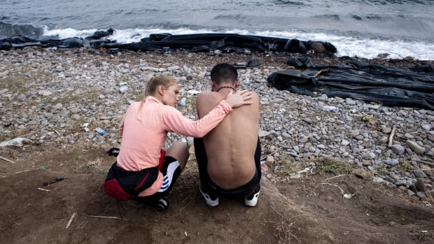 A volunteer tries to console a refugee on Sykamia beach, on the Greek island of Lesbos.