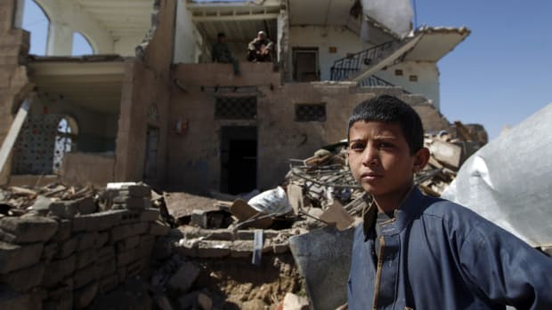 A boy stands near the rubble outside a house destroyed by Saudi-led airstrikes on the outskirts Sana'a, Yemen.