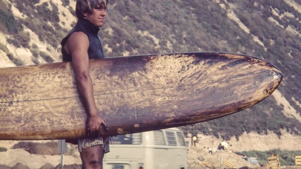 A surfer carries his oil-coated board.