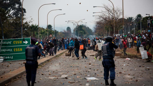 Residents throw stones during clashes with riot police in Johannesburg, South Africa, on May 8th, 2017, following a demonstration over land grabbing, housing, and unemployment in the area.