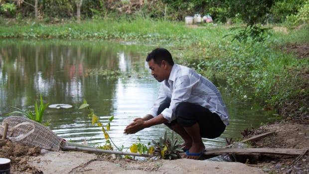 Nheb Thai washes his hand in his pond.