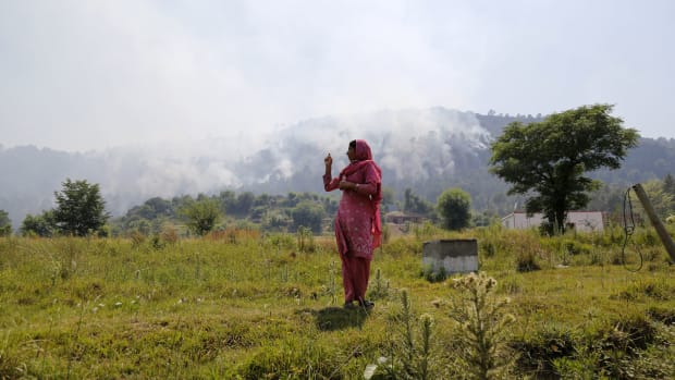 An Indian resident gestures toward rising smoke, believed to have resulted from mortar shelling, in the village of Jhangar, which lies very close to Pakistan on the Line of Control, on May 14th, 2017.