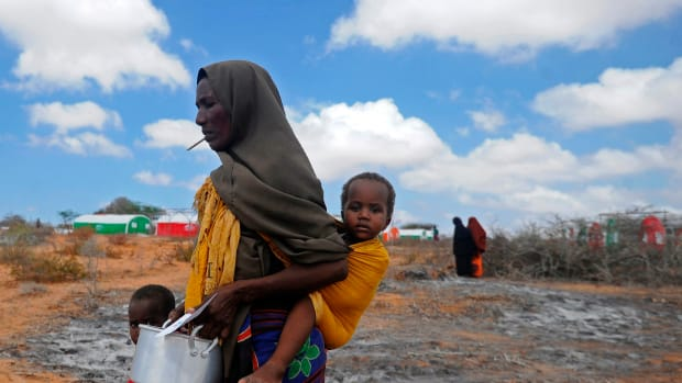 Newly displaced Somali women and children walk to a food distribution center at the Kaxda district on the outskirts of Mogadishu on April 9th, 2017.