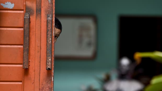 A migrant child watches behind the main door of a shelter in Tapachula, Mexico, where he's taken a rest during his attempt to reach the border between Mexico and the United States.