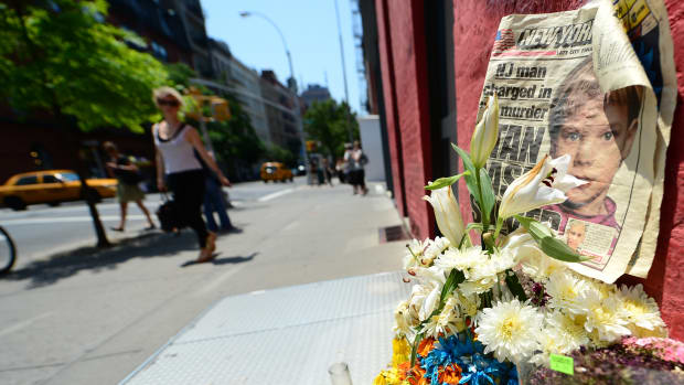 People walk past a street shrine to six-year-old Etan Patz, who disappeared 33 years ago, set in front of the building where suspect Pedro Hernandez confessed to having strangled the boy in New York.