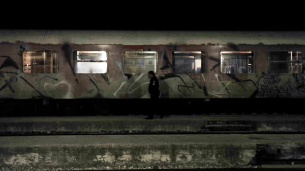 A Greek policeman patrols by a train at the railway station of Didymoteicho.