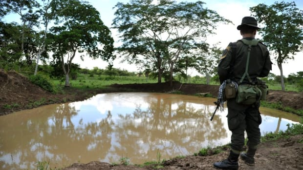 A police officer stands guard during a government land restitution process. Farmers were displaced under pressure and threats from former paramilitary commander Rodrigo Tovar Pupo.