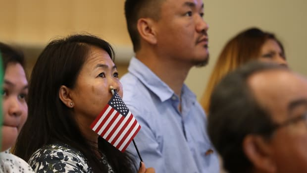 A newly naturalized citizen holds a U.S. flag after being sworn in as an American citizen during a naturalization ceremony on June 19th, 2017, in San Francisco, California. Twenty-nine former refugees from 17 different countries were sworn in during a ceremony to mark World Refugee Day, which falls on this date every year.