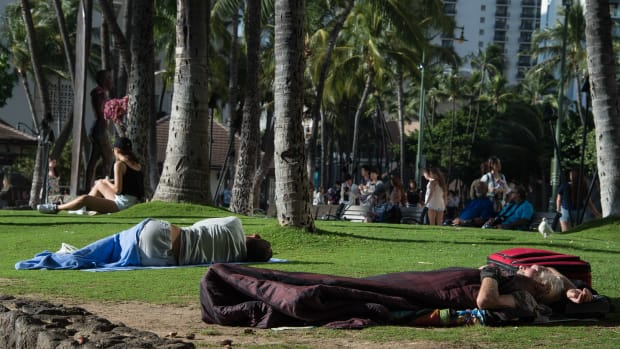 Homeless people sleep in a park off in Honolulu, Hawaii, on December 17th, 2016.
