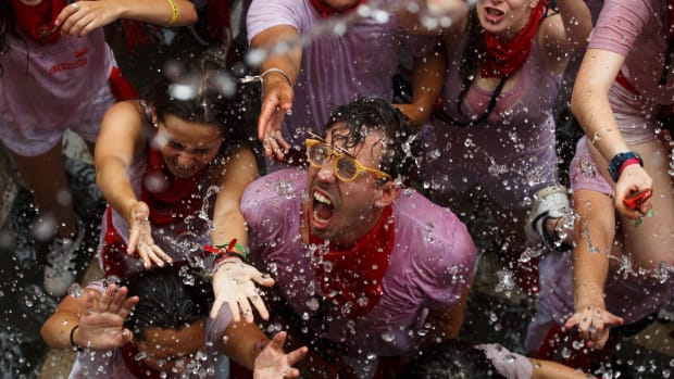 """Revellers enjoy the atmosphere during the opening day, or """"Chupinazo,"""" of the San Fermin Running of the Bulls fiesta on July 6th, 2017, in Pamplona, Spain. The annual Fiesta de San Fermin involves the daily running of the bulls through the historic heart of Pamplona to the bull ring."""