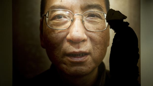A man walks in front of a poster of Liu Xiaobo at an exhibition at the Nobel Peace Center in Oslo, Norway, on December 9th, 2010.