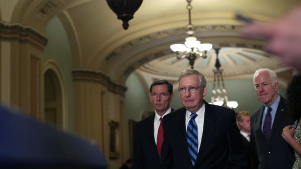 Senate Majority Leader Sen. Mitch McConnell (center) approaches the podium for a news briefing on July 11th, 2017, at the Capitol in Washington, D.C.