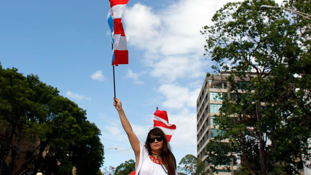 A woman waves a Puerto Rican flag during a protest against the referendum for Puerto Rico political status in San Juan, on June 11th, 2017.