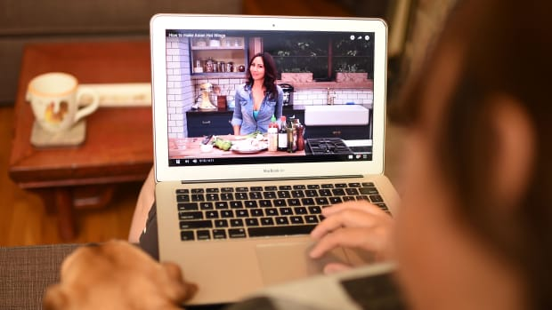 Woman watches a YouTube chef on her laptop.