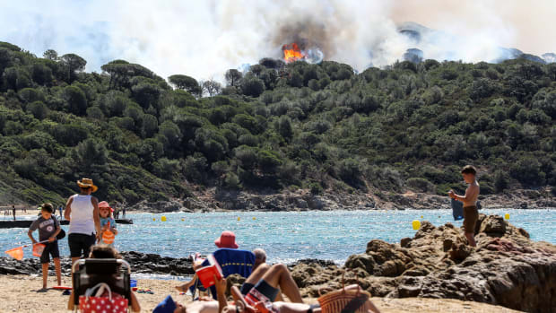 People enjoy the beach during a forest fire in La Croix-Valmer, France, on July 25th, 2017.