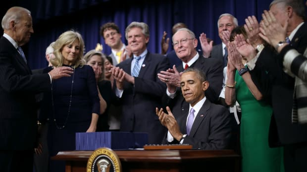 Surrounded by advocates and lawmakers, President Barack Obama applauds after signing the 21st Century Cures Act into law on December 13th, 2016, in Washington, D.C.