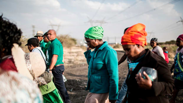 Widows of deceased striking miners who were killed during the Marikana massacre, walk from the memorial site, during the event's fifth anniversary in Marikana, on August 16, 2017. Thousands of South African miners sang remembrance songs on August 16, 2017, at the site of the 2012 Marikana massacre where police shot dead 34 strikers, as campaigners demanded prosecutions and compensation. The 34 miners were gunned down after police were deployed to break up a wildcat strike that had turned violent at the Lonmin-owned Marikana platinum mine, northwest of Johannesburg.