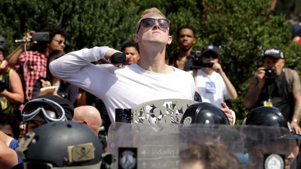 A man makes a slashing motion across his throat toward counter-protesters as he marches with other white nationalists and neo-Nazis during the Unite the Right rally on August 12th, 2017, in Charlottesville, Virginia.