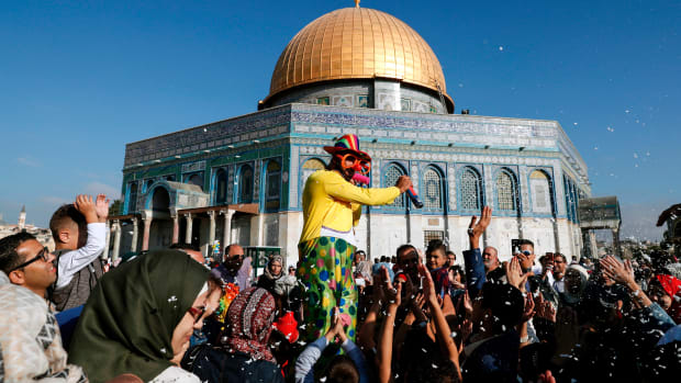 A man dressed in a clown outfit distributes balloons to children as confetti is thrown by the Dome of the Rock inside al-Aqsa Mosque compound, in Jerusalem's old city on the first day of Eid al-Adha on September 1st, 2017.