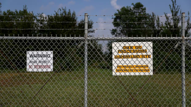 A sign is posted on a fence at the Dixie Oil Processors Superfund site on September 4th, 2017, in Friendswood, Texas.