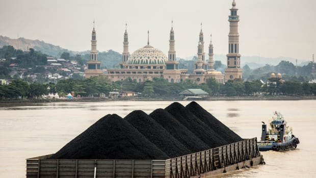 A tug pulls a coal barge past the Islamic centre on August 26th, 2016, in Samarinda, Kalimantan, Indonesia.