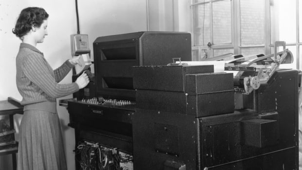 A woman operating a Hollerith Senior Rolling Total Tabulator in 1955.
