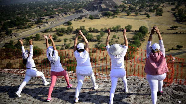 Women atop the Pyramid of the Sun at the archaeological site of Teotihuacan, Mexico, stretch and get energy from the rising sun during celebrations of the spring equinox on March 21st, 2018.