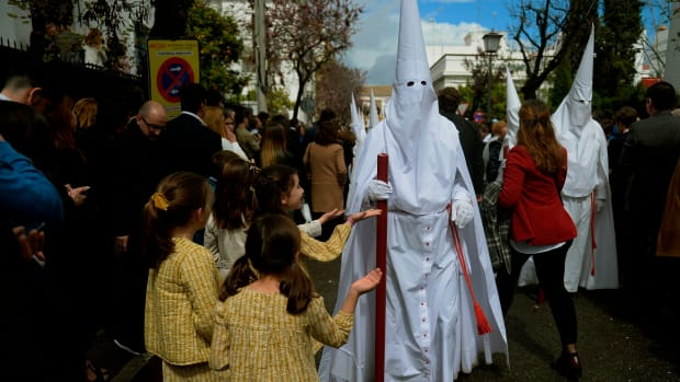 Children ask for candy from members of the La Paz brotherhood as they head to church to take part in the Palm Sunday procession in Sevilla, Spain, on March 25th, 2018.
