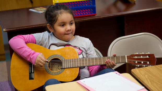 A young girl plays the guitar during guitar class at the Mariachi Academy in Harlem, New York.
