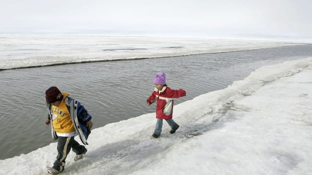 Inupiat Eskimo children play along the banks of the frozen Arctic Ocean on June 7th, 2006, in Browerville, Alaska.
