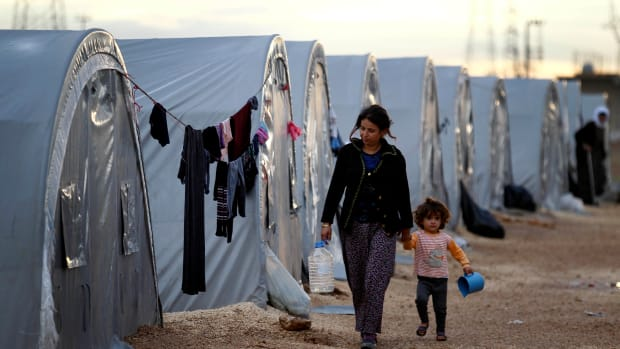 Kurdish refugees from the Syrian town of Kobani walk besides their tents in a camp in the southeastern town of Suruc on the Turkish-Syrian border.