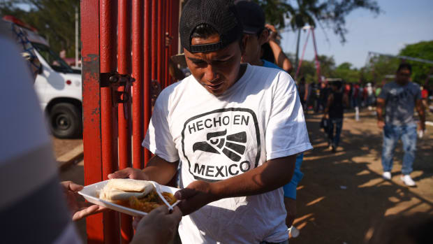 "Central-American migrants taking part in the ""Migrant Via Crucis"" caravan toward the United States receive breakfast as they camp at a sport complex in Matias Romero, Oaxaca State, Mexico."