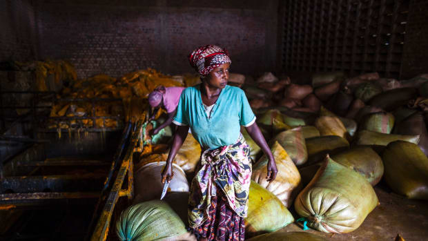 A woman holds a knife as she works with sacks containing palm oil at the Crystal Soap factory in Butembo.