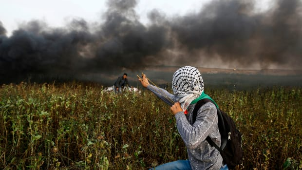A Palestinian protester uses a slingshot to throw stones toward Israeli forces during clashes following a protest along the border with Israel, east of Gaza City, on April 5th, 2018. Palestinians readied for new protests along the Gaza border and Israel warned that its open-fire rules would not change as fears of fresh violence rose a week after the bloodiest day in years.