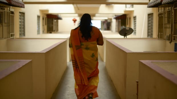 A trans Malaysian woman walks down an apartment corridor in Kuala Lumpur on September 23rd, 2014.