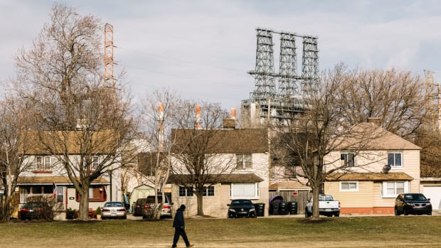 A man walks across a green space in Marktown, a historic district of East Chicago. The area is surrounded by heavy industry, including a BP tar sands refinery.