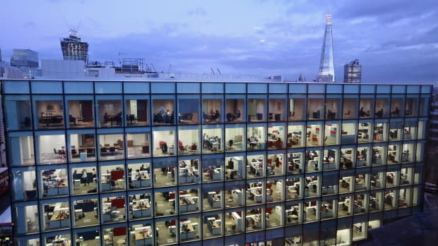 People work on various floors of an office building in London, England.