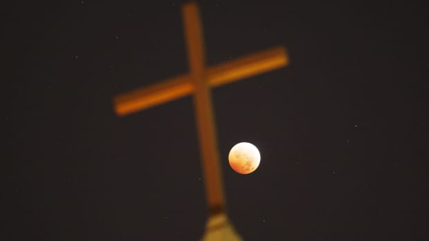 A religious cross is seen as the moon is illuminated by sunlight reflected off the Earth during a total lunar eclipse on October 8th, 2014, in Los Angeles, California.