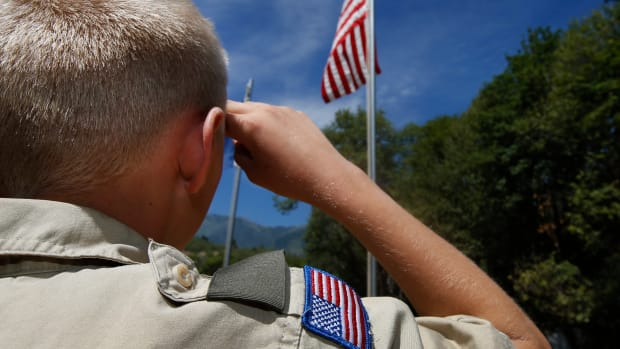 A Boy Scout salutes the American flag at on July 31st, 2015, outside Payson, Utah.