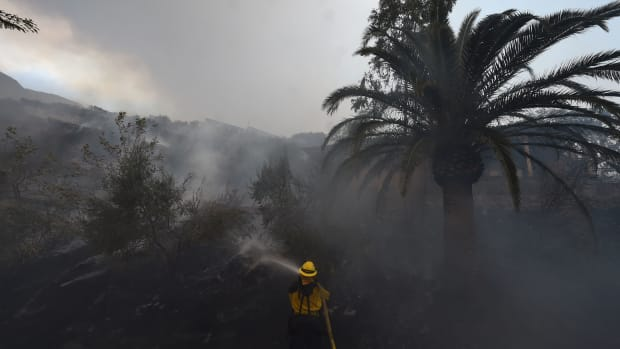 A firefighter puts out hotspots on a smoldering hillside in Montecito, California, as strong winds blow smoke and embers inland on December 16th, 2017.