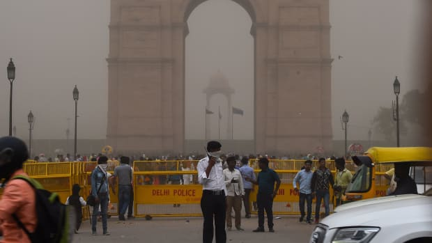An Indian traffic policeman covers his face as he stands on duty during a dust storm in New Delhi on May 2nd, 2018.