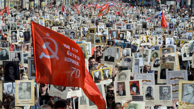 People carry portraits of World War II soldiers during the immortal regiment march, in which Russia marks the 73rd anniversary of the Soviet Union's victory over Nazi Germany, in downtown Saint Petersburg on May 9th, 2018.