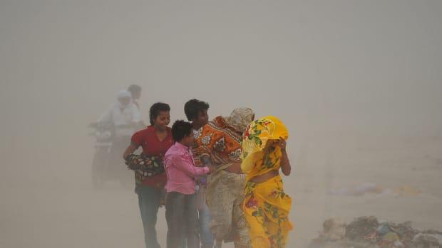 Indian Hindu devotees walk through a dust storm at the Sangam.
