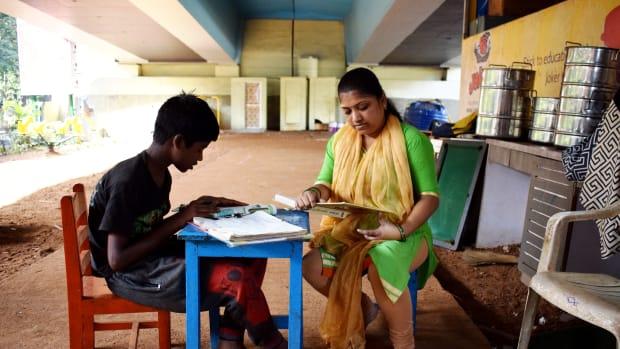 A teacher sits with Vishal Pawar at Signal School.