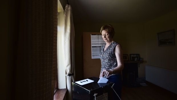 Maureen Ui Fhearraigh casts her ballot paper as voting takes place a day earlier than on the mainland, on May 24th, 2018, in Gola Island, Ireland.