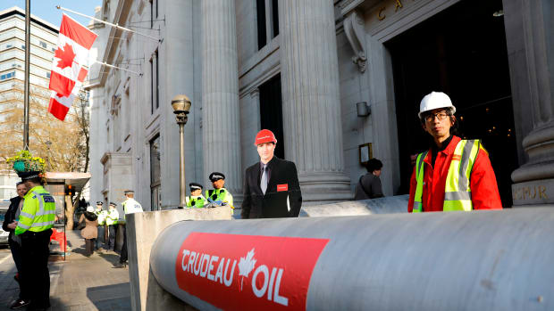 Demonstrators use a mock oil pipeline to block the entrance to the Canadian Embassy in central London on April 18th, 2018, as they protest against the Trans Mountain oil pipeline from Alberta's oil sands to the Pacific Ocean.